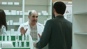 Pharmacist and client have conflict and try to solve the problem at pharmacy stock footage