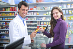 Pharmacist and client at pharmacy. Customer buying medicine at the pharmacy