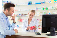 Pharmacist and client at pharmacy. Smiling Stock Images