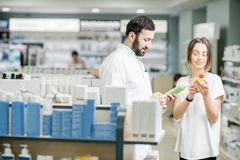 Pharmacist with client at the pharmacy store. Pharmacist helping young women client to choose cosmetics at the pharmacy store stock images