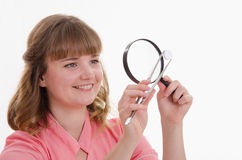 Pharmacist closely examines tablet under a magnifying glass Royalty Free Stock Image