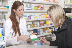 Pharmacist compares product. Friendly pharmacist recommends a product to her customer Royalty Free Stock Image