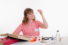 Pharmacist considers powder in a test tube Royalty Free Stock Images
