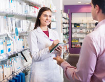 Pharmacist and consulting man in pharmacy Stock Image