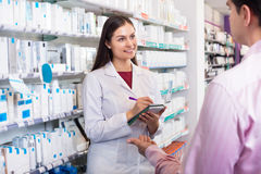 Pharmacist and consulting man in pharmacy. Helpful pharmacist serving and a consulting men in a pharmacy Royalty Free Stock Image
