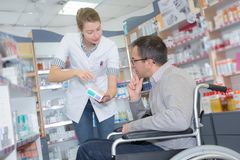 Pharmacist consulting man in wheelchair in pharmacy. Pharmacist consulting a men in a wheelchair in pharmacy Stock Image