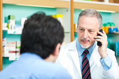 Pharmacist and costumer. Smiling pharmacist talking on the phone stock photo