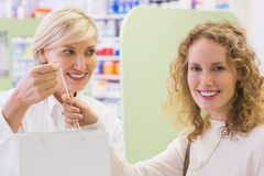 Pharmacist and costumer holding paper bag Royalty Free Stock Photos