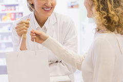 Pharmacist and costumer holding paper bag Royalty Free Stock Image