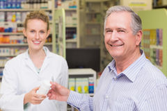 Pharmacist and costumer smiling a camera Stock Image