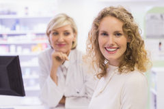 Pharmacist and costumer smiling at camera Stock Photography