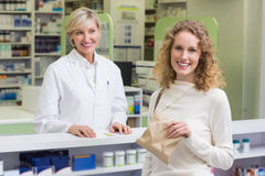 Pharmacist and costumer smiling a camera Royalty Free Stock Photos