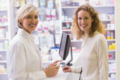 Pharmacist and costumer smiling at camera Royalty Free Stock Image