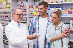 Pharmacist and costumers smiling Stock Images