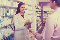 Pharmacist counseling customer about drugs. Positive female pharmacist counseling customer about drugs usage in modern farmacy Stock Photo