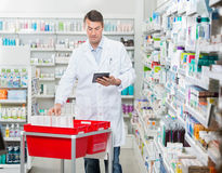 Pharmacist Counting Stock While Using Digital Tablet Royalty Free Stock Photography