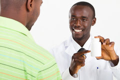 Pharmacist and customer. African american pharmacist explaining how to take the medicine to customer Stock Images
