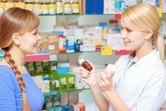 Pharmacist and a customer choosing medicine Royalty Free Stock Photos