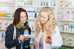 Pharmacist And Customer Reading Prescription Paper Stock Photo