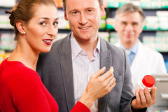 Pharmacist with customers in pharmacy Royalty Free Stock Photography