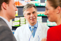 Pharmacist with customers in pharmacy Stock Photo