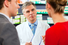 Pharmacist with customers in pharmacy Stock Photography