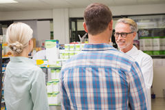 Pharmacist and customers talking about medication Royalty Free Stock Photo