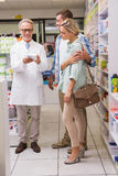 Pharmacist and customers talking about medication Stock Images