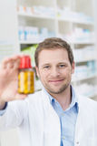 Pharmacist displaying a bottle of pills Royalty Free Stock Photo