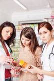 Pharmacist, doctor and client inside pharmacy Stock Photography
