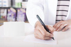 pharmacist or doctor writing with green tablet package with copy space stock image