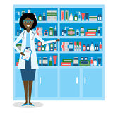 Pharmacist in drug store. Beautiful smiling african american woman in white standing near shelf with medication. Woman in glasses Stock Images