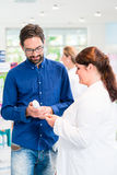 Pharmacist or drug store sales woman advising customer. Pharmacist or drug store sales women advising customer on care products for men Stock Images