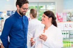 Pharmacist or drug store sales woman advising customer Royalty Free Stock Photos