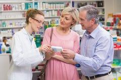 Pharmacist explaining the drug to costumers. At pharmacy Stock Image