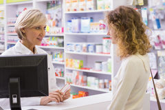 Pharmacist explaining the drug to patient. In the pharmacy Royalty Free Stock Photography
