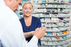 Pharmacist Explaining Product Details To Customer Royalty Free Stock Images