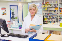 Pharmacist files documents. At pharmacy Royalty Free Stock Image