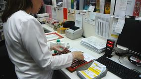 Pharmacist filling multi dose pack with medications. A pharmacist fills a multi dose pack with medications at an australian pharmacy stock video footage