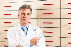 Pharmacist in front of medicine chest Stock Image