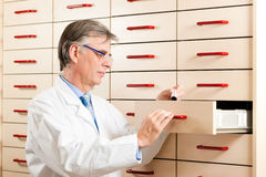 Pharmacist in front of medicine chest Royalty Free Stock Photo