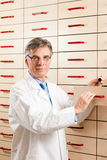 Pharmacist in front of medicine chest Royalty Free Stock Images