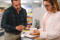 Pharmacist giving advice over a medicine to customer stock photo