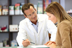 Pharmacist giving advice to patient. Veterinarian giving medical advice to client Royalty Free Stock Images