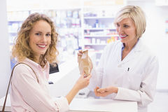 Pharmacist giving bag paper to costumer Royalty Free Stock Photo