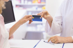 Pharmacist giving credit card to costumer Stock Photo