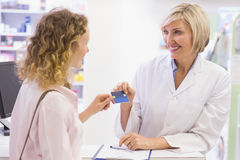Pharmacist giving credit card to costumer Royalty Free Stock Image