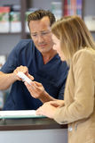 Pharmacist giving medical instructions to patient Royalty Free Stock Photography