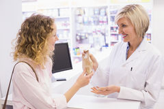 Pharmacist giving medicine to costumer Royalty Free Stock Photos