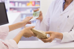 Pharmacist giving medicine to costumer Stock Photography